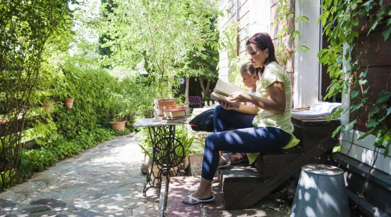 lady and daughter sitting on stairs reading book