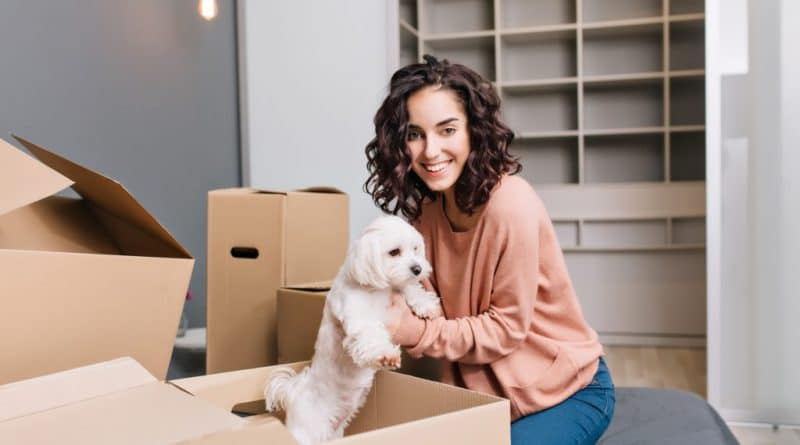 lady holding dog in box